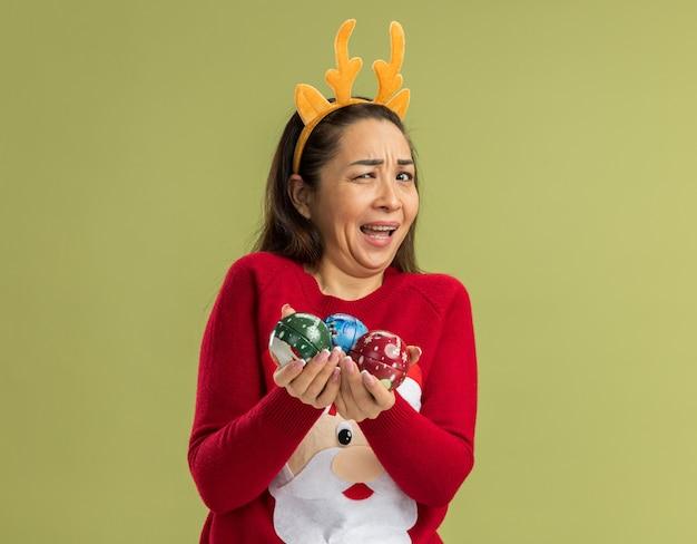Mulher jovem com suéter vermelho de natal, vestindo uma borda engraçada com chifres de veado segurando bolas de natal, sorrindo e confusa