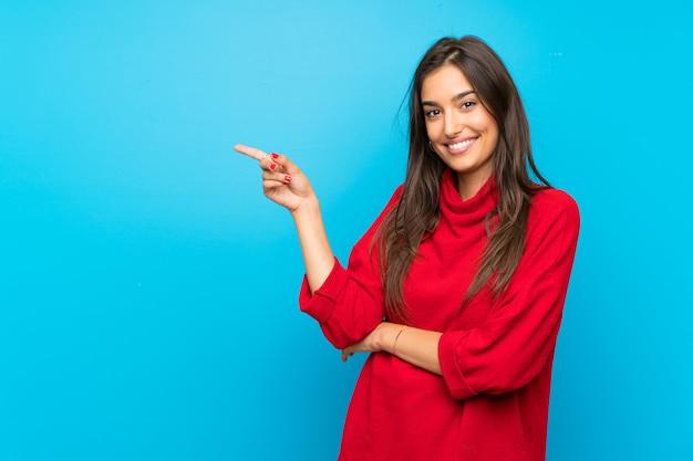Mulher jovem, com, suéter vermelho, isolado, azul, apontando dedo, ao lado