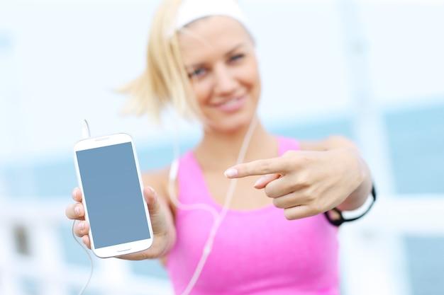Mulher jovem com sutiã esportivo rosa mostrando o telefone sobre o mar