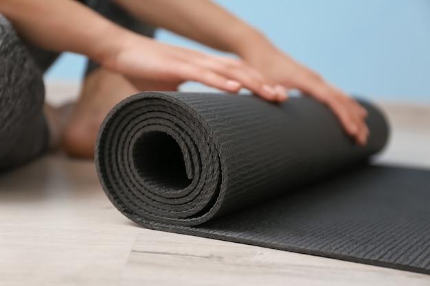 Mulher jovem com tapete de ioga dentro de casa, close-up