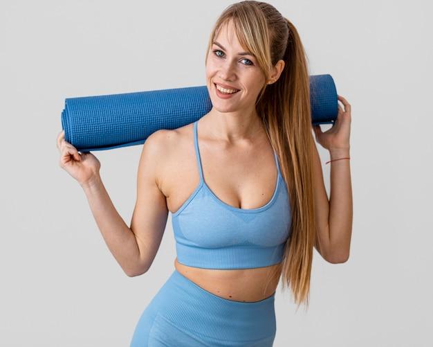 Mulher jovem com tapete de ioga