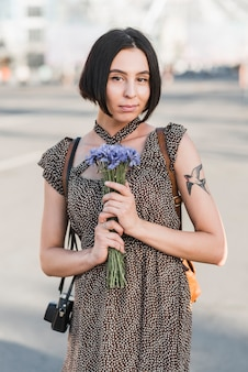 Mulher jovem, com, tatuagem, segurando, flores