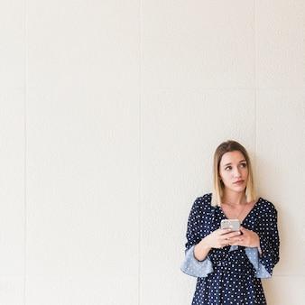 Mulher jovem, com, telefone móvel, olhando