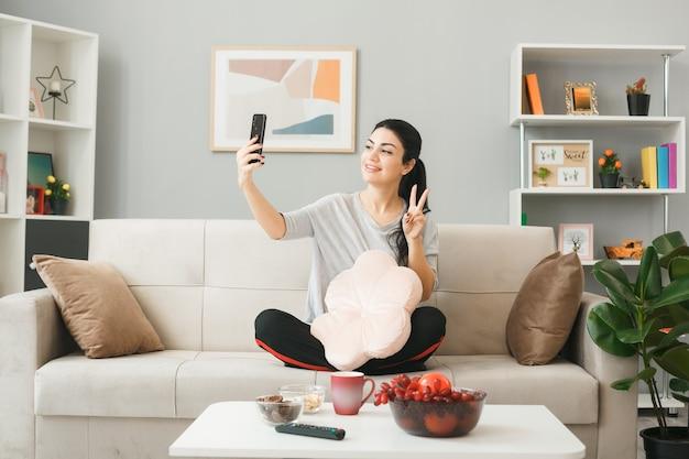Mulher jovem com travesseiro mostrando gesto de paz tira uma selfie sentada no sofá atrás da mesa de centro da sala de estar