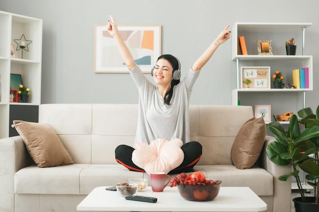 Mulher jovem com travesseiro usando fones de ouvido, sentada no sofá atrás da mesa de centro na sala de estar