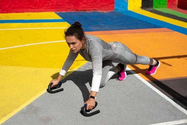 Mulher jovem com um agasalho cinza fazendo flexões no chão do parquinho