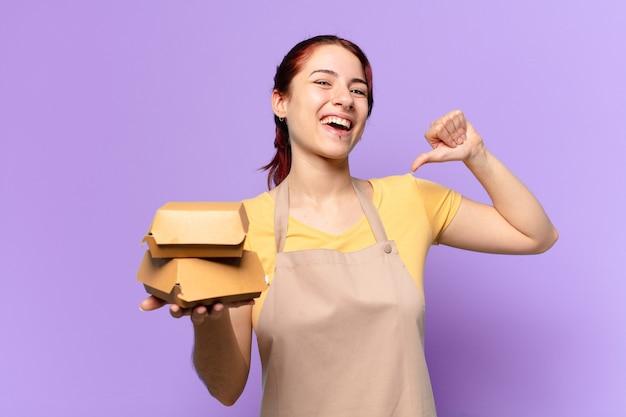 Mulher jovem com um avental e um hambúrguer para levar