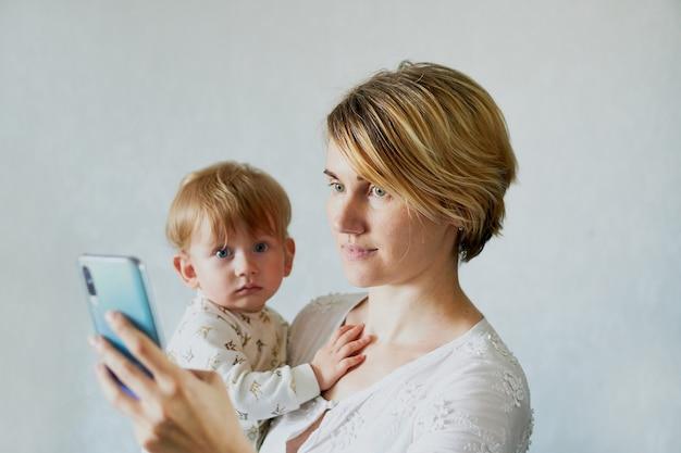 Mulher jovem com um bebê nos braços liga ao telefone