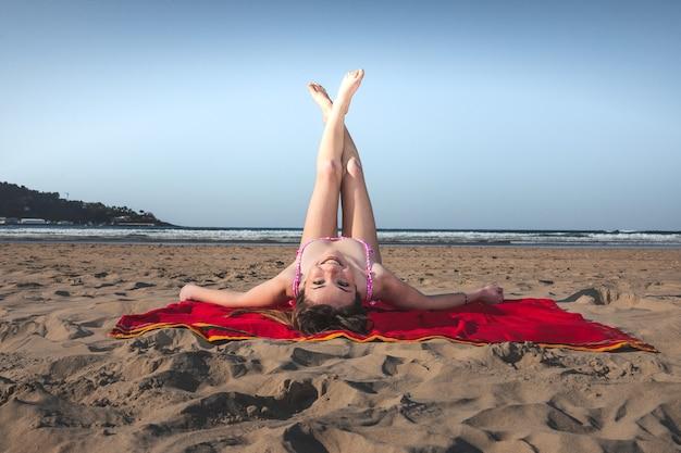Mulher jovem com um biquíni rosa em uma toalha vermelha na praia