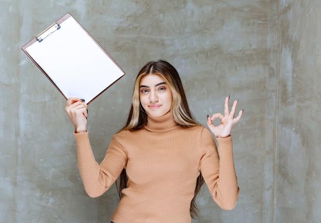 Mulher jovem com um bloco de notas mostrando um gesto de ok em uma pedra