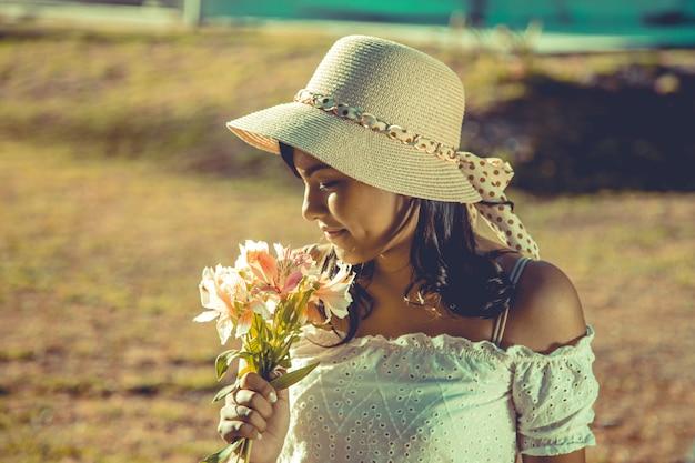 Mulher jovem, com, um, buquê flores, ligado, um, pôr do sol