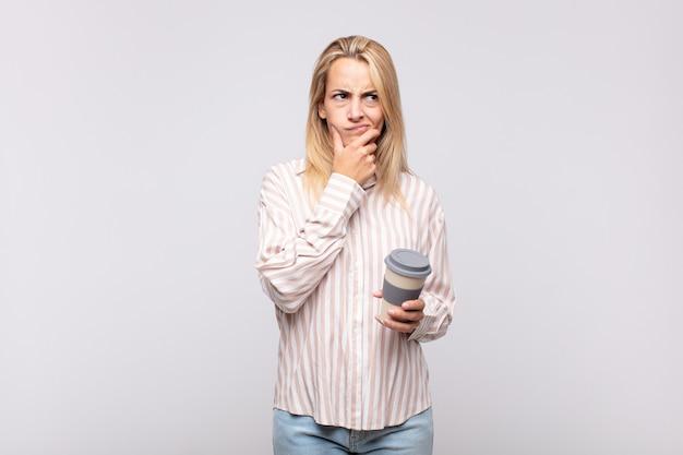 Mulher jovem com um café pensando, sentindo-se duvidosa e confusa, com opções diferentes, se perguntando qual decisão tomar