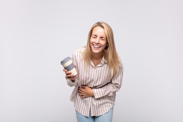 Mulher jovem com um café rindo alto de uma piada hilária, sentindo-se feliz e alegre, se divertindo