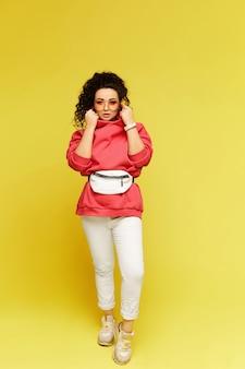 Mulher jovem com um capuz rosa, calça branca e óculos escuros posando Foto Premium