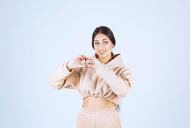 Mulher jovem com um capuz rosa fazendo poses lindas e emocionantes