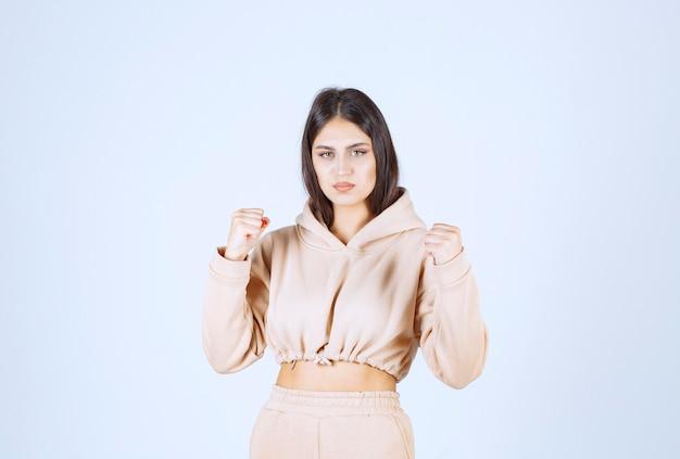 Mulher jovem com um capuz rosa se sentindo forte e poderosa