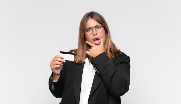 Mulher jovem com um cartão de crédito com a boca e os olhos bem abertos e a mão no queixo, sentindo-se desagradavelmente chocada, dizendo o quê ou uau