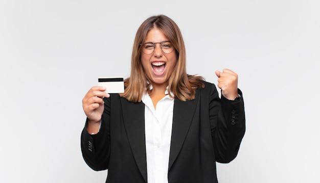 Mulher jovem com um cartão de crédito gritando agressivamente com uma expressão de raiva ou com os punhos cerrados celebrando o sucesso