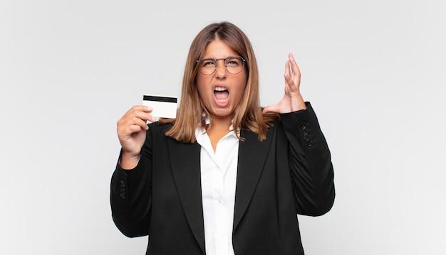 Mulher jovem com um cartão de crédito gritando com as mãos para cima, sentindo-se furiosa, frustrada, estressada e chateada