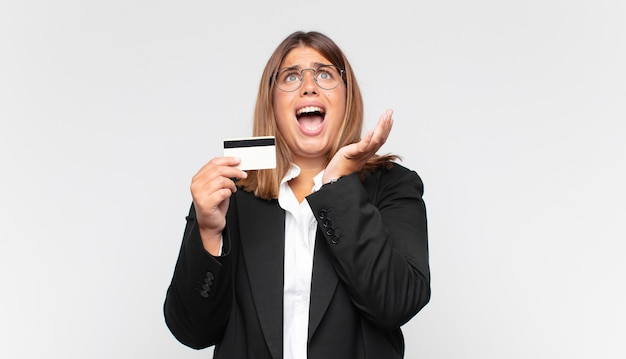 Mulher jovem com um cartão de crédito parecendo desesperada e frustrada, estressada, infeliz e irritada, gritando e gritando