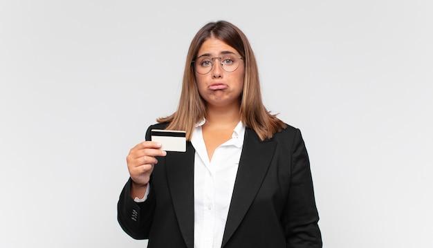 Mulher jovem com um cartão de crédito se sentindo triste e chorona com uma aparência infeliz, chorando com uma atitude negativa e frustrada