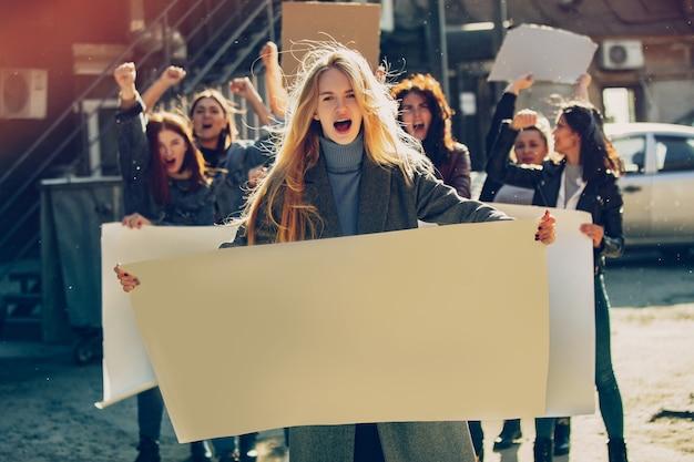 Mulher jovem com um cartaz em branco na frente de pessoas protestando sobre os direitos das mulheres