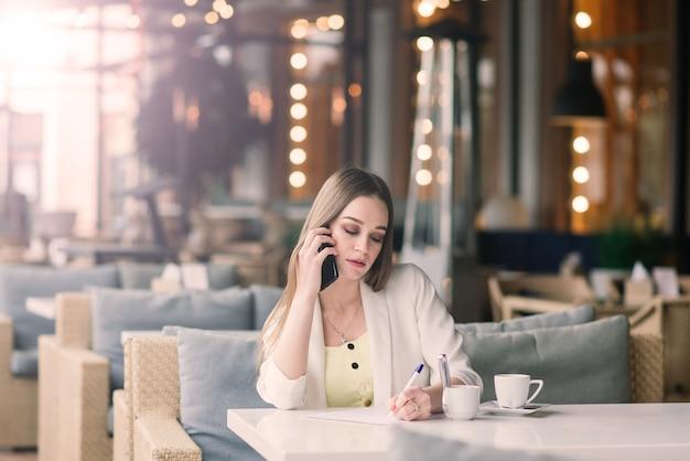 Mulher jovem com um casaco branco a trabalhar num café com jornais, a beber café