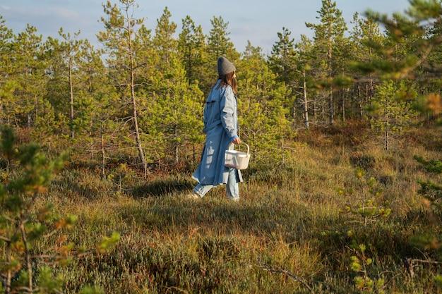 Mulher jovem com um casaco elegante e um chapéu caminhando pela floresta de outono em um dia quente e ensolarado em busca de cranberry
