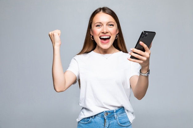 Mulher jovem com um celular comemorando uma vitória isolada