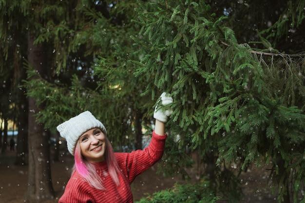 Mulher jovem com um chapéu de malha e luvas brancas posando contra um pinheiro e caindo neve.