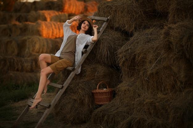 Mulher jovem com um chapéu de palha em estilo rústico sentada descansando no campo em uma velha escada de madeira
