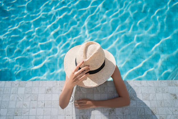 Mulher jovem com um chapéu de sol está sentada à beira da piscina de um resort.