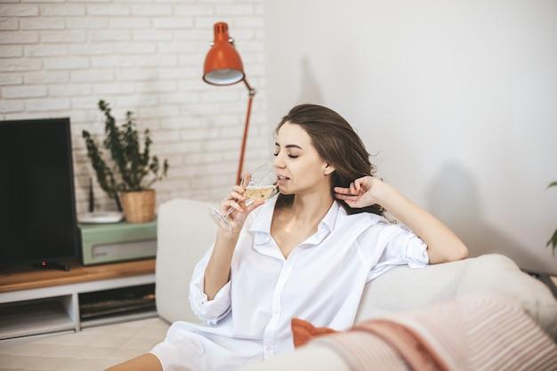 Mulher jovem com um copo de vinho em casa. a pessoa do sexo feminino relaxa bebendo vinho.