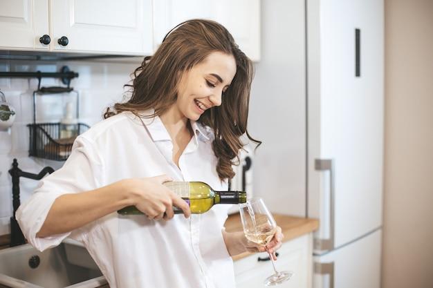 Mulher jovem com um copo de vinho em casa. mulher relaxa bebendo vinho na cozinha.