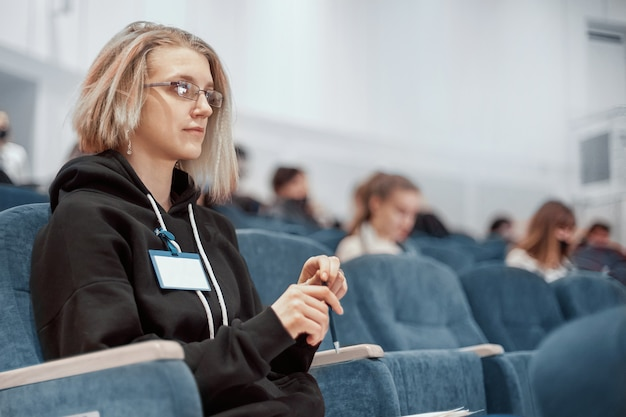 Mulher jovem com um distintivo em branco sentada na sala de conferências
