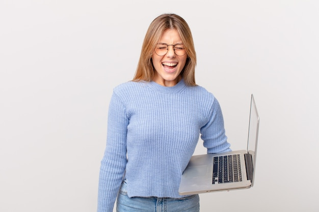 Mulher jovem com um laptop gritando agressivamente e parecendo muito zangada