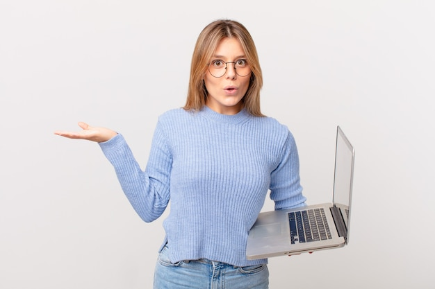 Mulher jovem com um laptop parecendo surpresa e chocada, com o queixo caído segurando um objeto