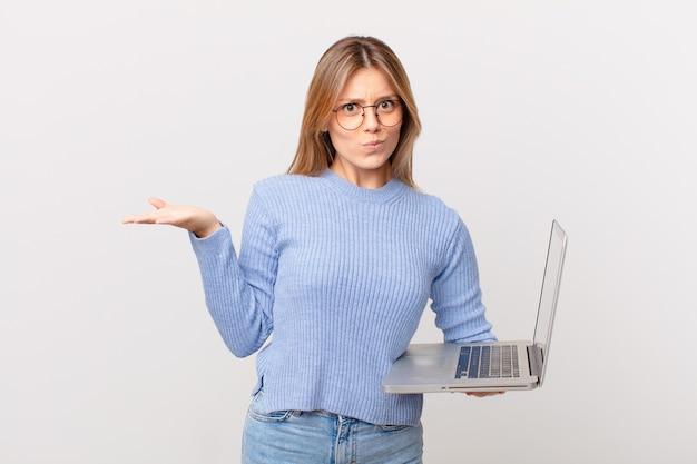 Mulher jovem com um laptop se sentindo intrigada, confusa e em dúvida