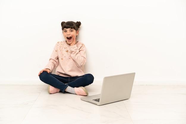 Mulher jovem com um laptop sentada no chão com expressão facial de surpresa e choque