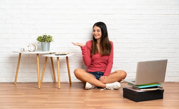 Mulher jovem com um laptop sentada no chão em um ambiente fechado, segurando copyspace imaginário na palma da mão para inserir um anúncio