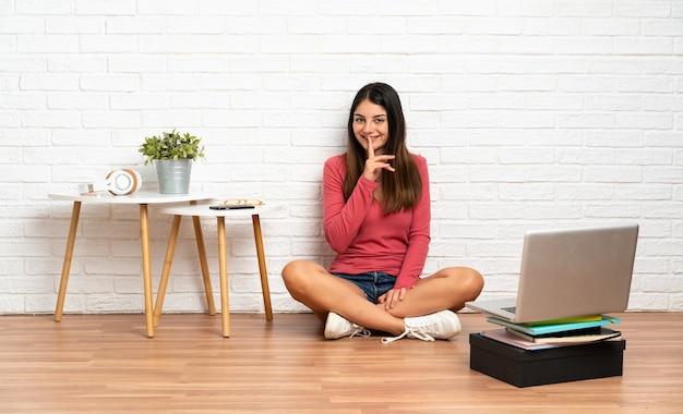 Mulher jovem com um laptop sentada no chão em uma área interna, mostrando um sinal de silêncio, gesto colocando o dedo na boca