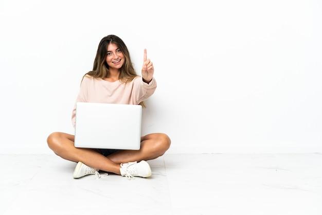 Mulher jovem com um laptop sentada no chão, isolada na parede branca, mostrando e levantando um dedo