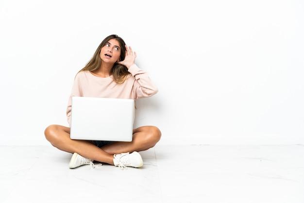 Mulher jovem com um laptop sentada no chão, isolada na parede branca, ouvindo algo colocando a mão na orelha