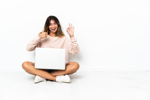 Mulher jovem com um laptop sentada no chão, isolada no branco, mostrando o sinal de ok e o polegar para cima
