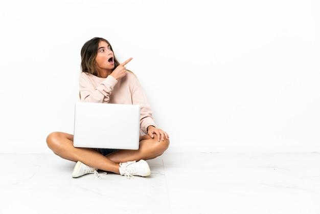 Mulher jovem com um laptop sentada no chão isolada