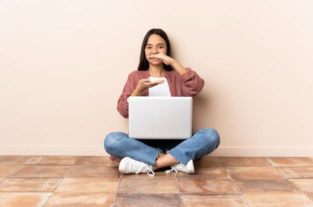 Mulher jovem com um laptop sentada no chão, segurando o imaginário de copyspace na palma da mão para inserir um anúncio