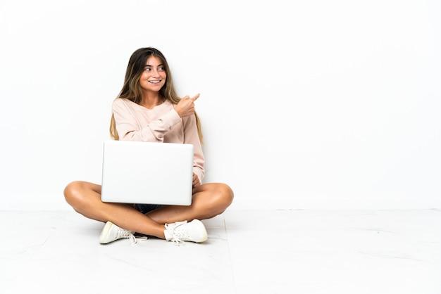 Mulher jovem com um laptop sentado no chão, isolado no fundo branco, apontando para trás