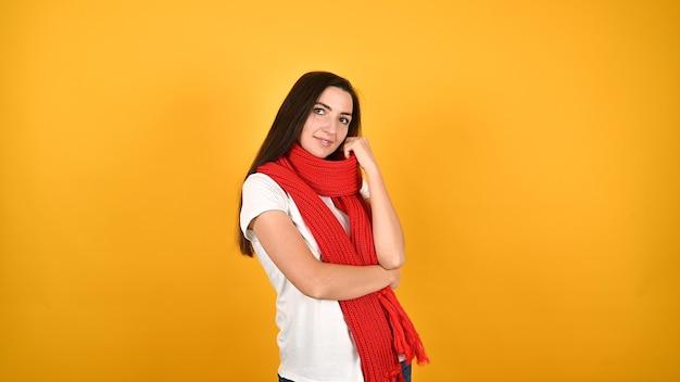 Mulher jovem com um lenço vermelho em uma parede amarela