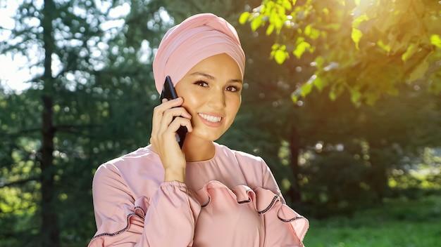 Mulher jovem com um lindo turbante e um vestido da mesma cor rosa suave está falando ao telefone contra o fundo de árvores