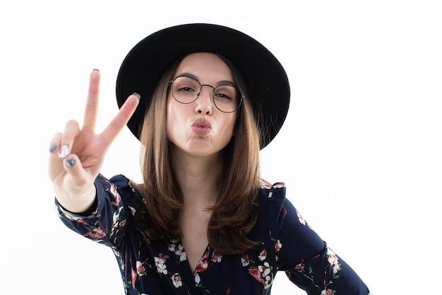 Mulher jovem com um longo vestido floral e um chapéu posa para a câmera